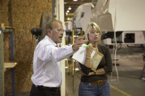 Dutchmen president Don Clark pointing out a production process to news reporter.